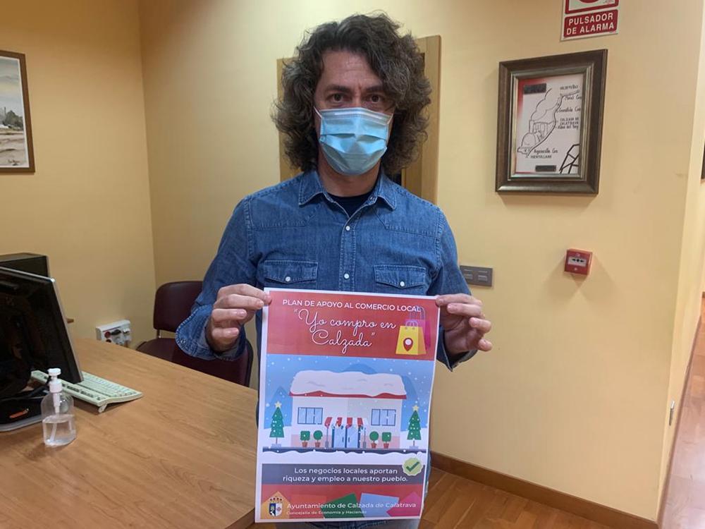 Ramón Fernández Espinosa mostrando el cartel del Plan de Apoyo al comercio local de Calzada de Calatrava